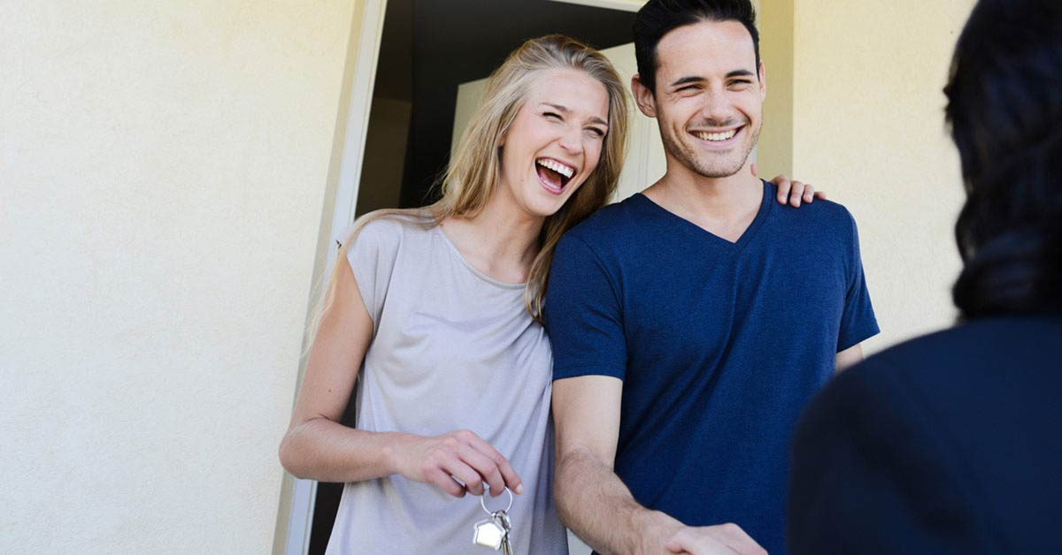 Young couple smiling and holding keys to their first home