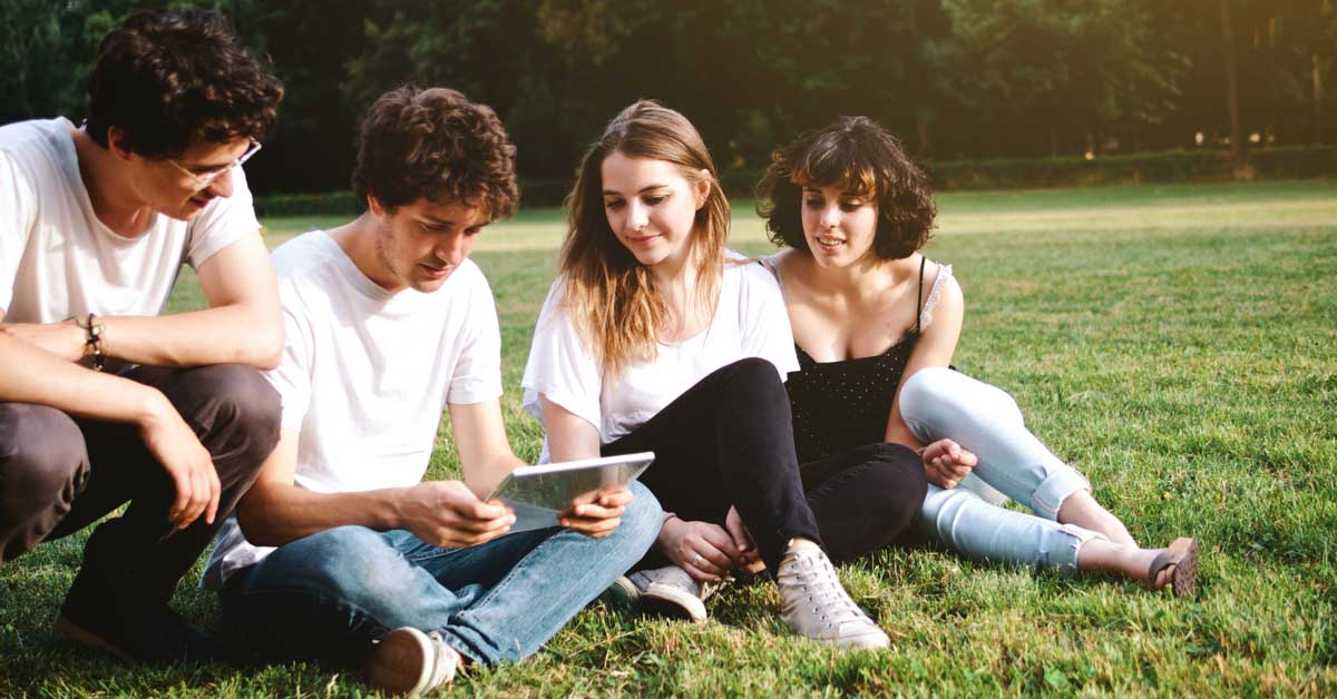 Four students sitting together on the lawn at their University Campus, looking at a tablet screen studying