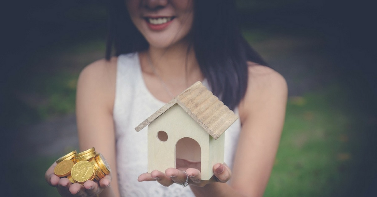 Lady holding coins and toy house