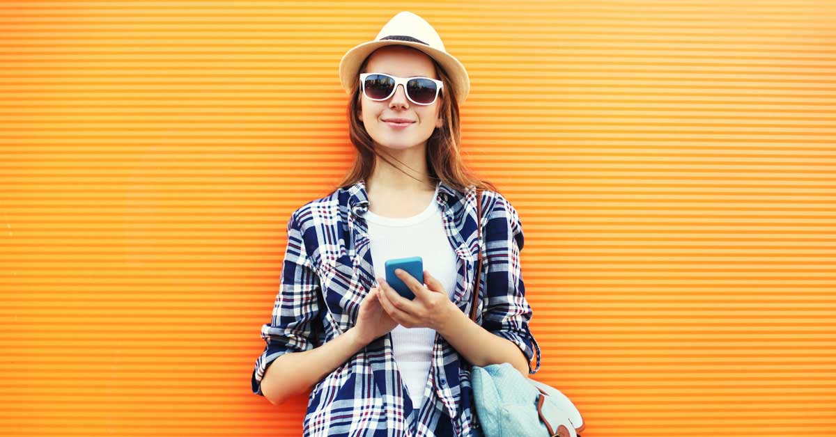 Woman standing in front of orange wall, smiling with sunglasses and a hat on, holding her mobile phone.