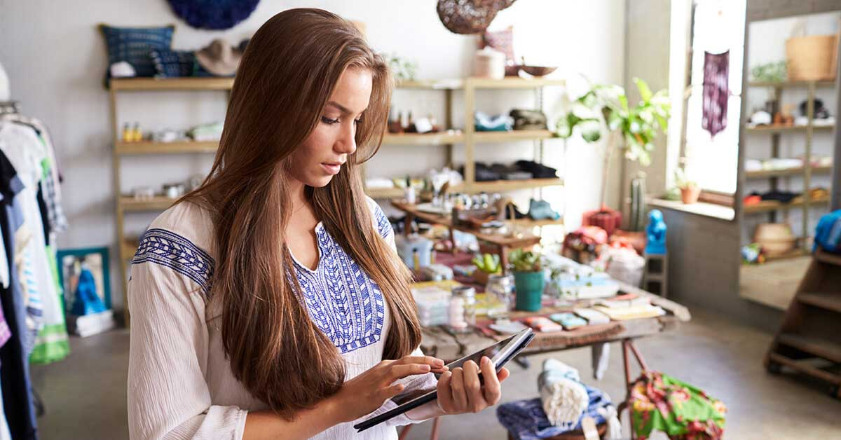 Young woman small business owner in her clothing store using a tablet to send an invoice using a Pay ID