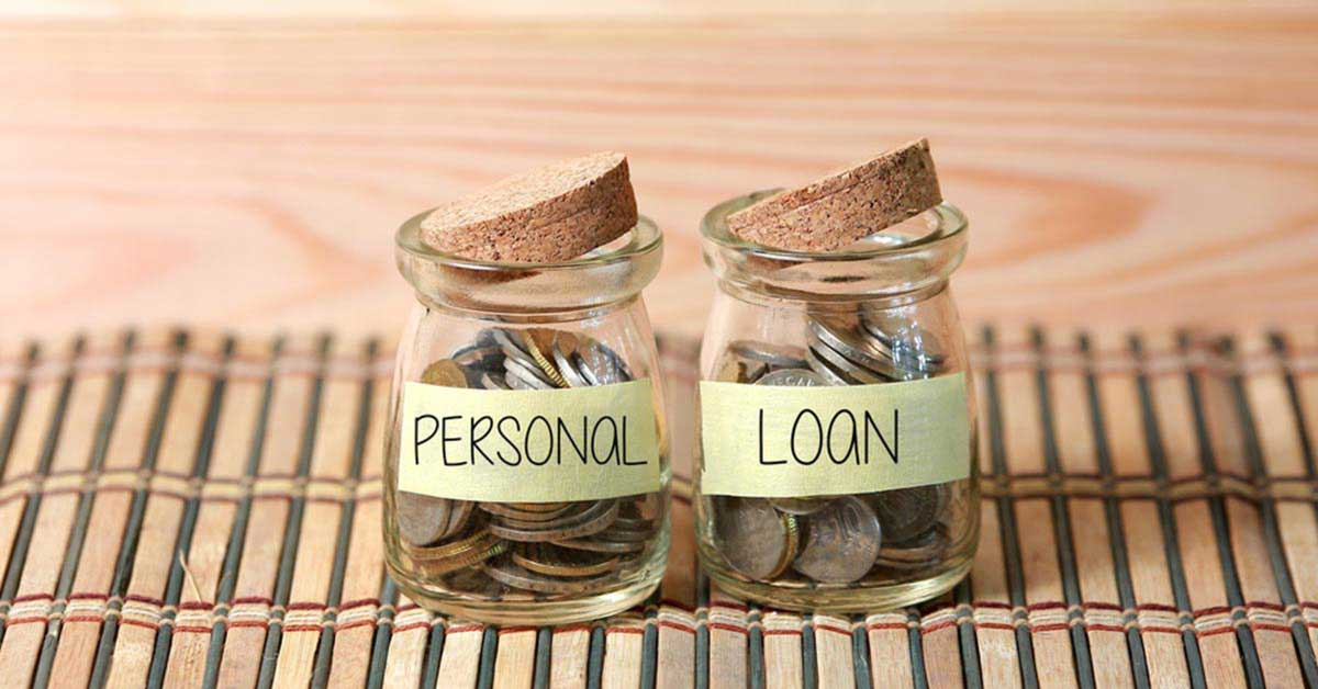 Two jars with cork lids filled with coins on a wooden table with a note in the first jar saying Personal and a note in the second jar saying Loan.