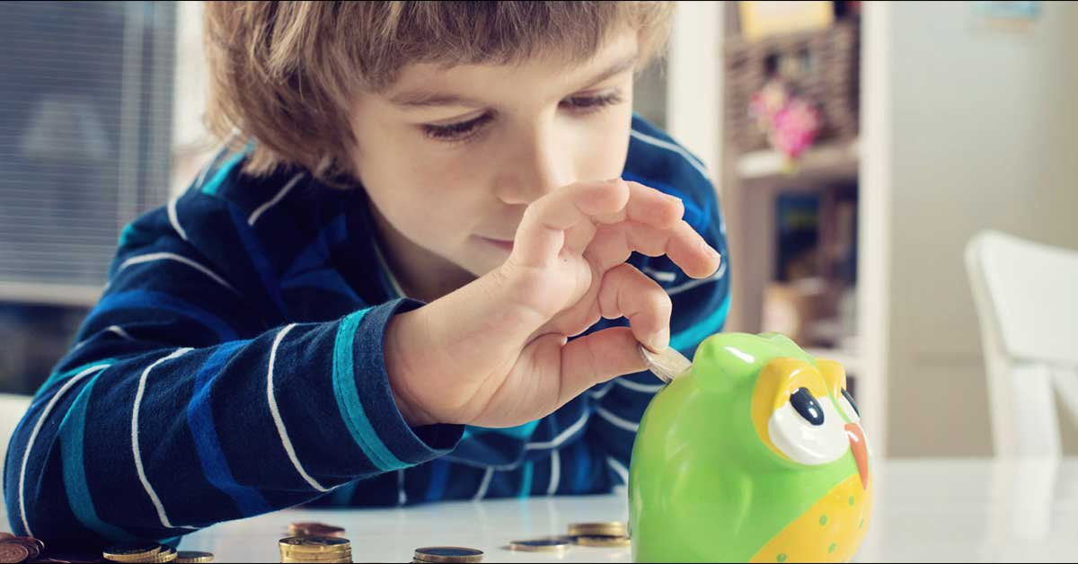 Young boy in a blue striped shirt placing a coin into a green and yellow owl coin bank