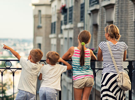 Children and mother overlooking balcony in Italy